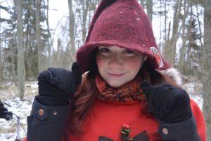 Hymyilevä punapukuinen tonttutyttö jolla tonttulakki päässä. Taustalla luminen metsä. Tytöllä on punaiset posket.