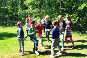 Lapsia leirillä kesäisesä maisemassa, tyttöjä ja poikia