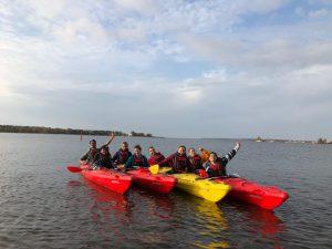 Ryhmä nuoria melomassa kajakeilla merellä