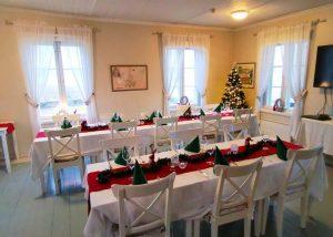 Kaunis punavalkoinen joulukattaus vanhan porvarishuvilan salissa. Valkoiset juhlaliinat ja punaiset kaitaliinat, kynttilöitä.