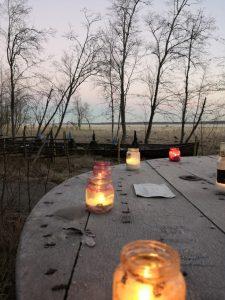 Vanha puinen pöytä luonnossa, takana siintää meri. Harmaalla kuluneen näköisellä pöydällä kynttilälyhtyjä.