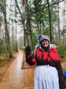 Tonttutyttö, jolla on valkoinen esiliina ja harmaa tonttulakki, metsäisellä pitkospuupolulla.