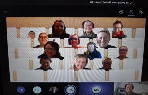 Kuvassa osallistujia kokouspöytiensä ääressä