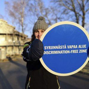 Nuori nainen pitää kädessään julistetta Syrjinnästä vapaata aluetta