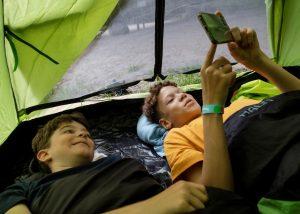 Kaksi poikaa lukee kirjoja vihreässä teltassa