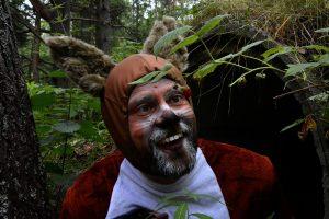 Hymyilevä mieshenkilö metsässä päällään oravapuku.